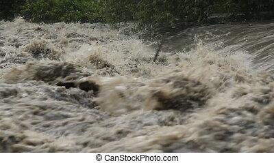Flood river. Turbulent water.