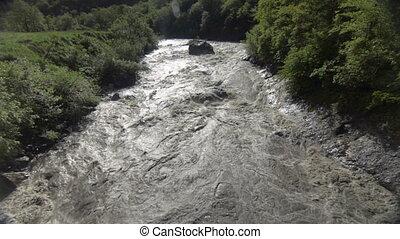 Flood water fast flowing down swollen mountain river in Georgia