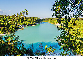 Flooded kaolin quarry on a cloudless summer day. Russia, Ural