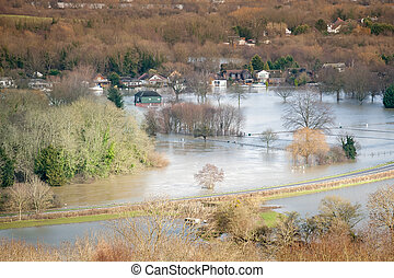 landscape of luxury homes and farmland under river thames floodwater near windsor, uk