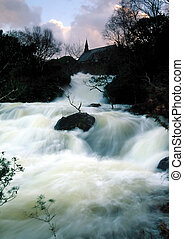 flooded river in Killarney National Park, Co.Kerry, Ireland with small church in background