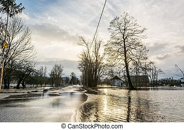 Flooded road - Road flooded after spring thaw with sun ...