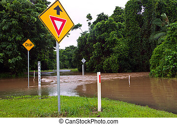 Flooded road with depth indicators and give way and dip road signs  after heavy rain and flooding in Queensland, Australia