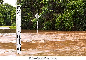 Flooded road with depth indicators in Queensland, Australia...