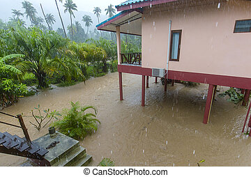 Flooded street with palm trees and house in island Koh Phangan, Thailand