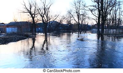 Flooding of river in spring in town during melting of snow. Flooding in city. Flood between private houses. Flood on river in spring. Natural disaster. Big water in city