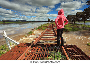 Floodwaters run under buckled train tracks - A female looks...