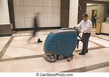 Floor cleaning machine operator in commercial building lobby