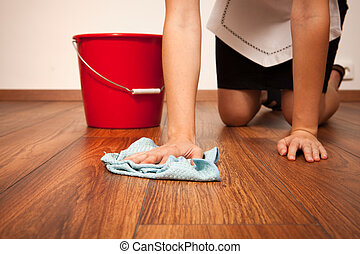 Woman cleaning the floor with blue cloth