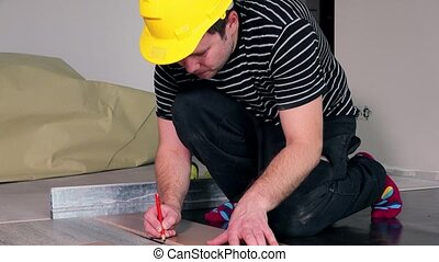 Floor laying man with pencil make markings on laminate board