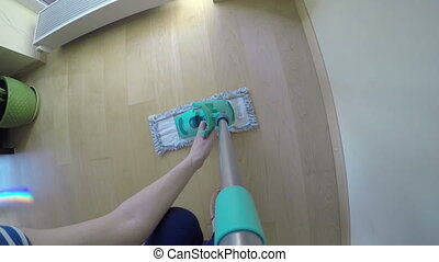 floor mopping home - woman hand mopping hardwood floor at...