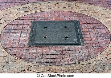 Floor tiles in the village - Metal drain lid on the street...