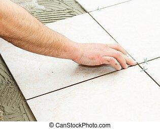 Handyman doing renovation works - floor tiling.