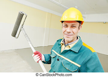 flooring worker with roller - male plasterer portrait during...