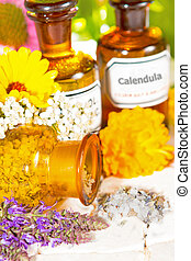 A brown glass bottle tipped on its side spilling dired crushed flower petals with fresh lavender and calendula, or pot marigold, for floral aromatherapy treatments, essential oil and plant extracts