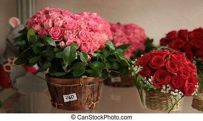 Floral arrangements in form of heart on shelf in flower shop