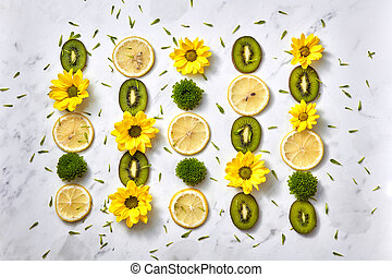 Floral background. Flowers pattern from yellow, green flowers, slices of kiwi and lemon. Flat lay.