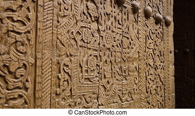 Floral carvings on a wooden door in Uzbekistan - A close-up,...