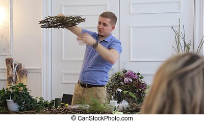 Floral designer holds studying courses of florists in art studio.