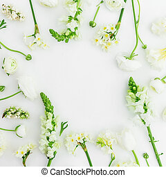 Floral frame of white flowers on white background. Flat lay, top view.