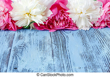 Floral frame with pink peonies on wooden background