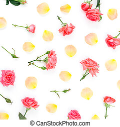 Floral pattern made of red roses flowers and orange rose petals on white background. Flat lay, top view.