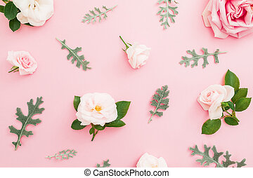 Floral pattern made of roses and leaves on pastel pink background. Flat lay, top view.