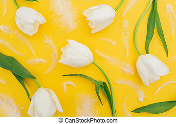 Floral pattern made of white tulip flowers and feathers on yellow background. Flat lay, top view.