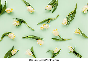 Floral pattern made of yellow tulip on green background. Flat lay, top view. Valentine's background. Floral pattern. Pattern of flowers.