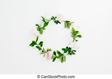 Floral round frame of pink roses and green leaves on white background. Flat lay, top view.