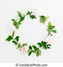 Floral round frame of roses and green leaves on white background. Flat lay, top view. Spring time composition