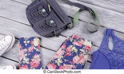 Floral trousers and blue top. Denim bag and canvas shoes. ...