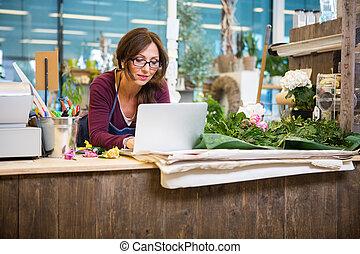 floricultor, usando computador portátil, em, contador, em,...