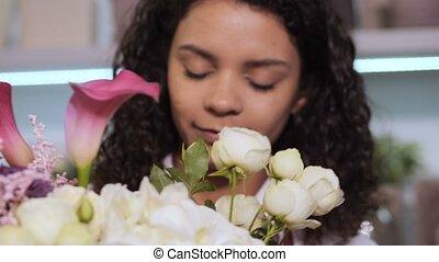Florist adding rose sprig to flower arrangement - Closeup of...