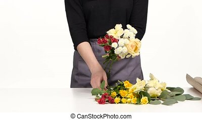 Florist adds of flowers in the bouquet. White. Slow motion. Close up
