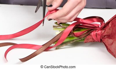 Florist adjusts bow from a ribbon on a bouquet of flowers. White. Close up