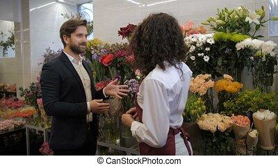 Florist advising client flowers for composition -...