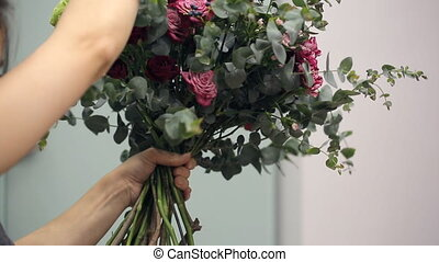 Florist Asian collects a bunch of red, pink and white roses and berries.