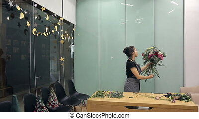 Florist Asian collects a bunch of red, pink and white roses in a large room.