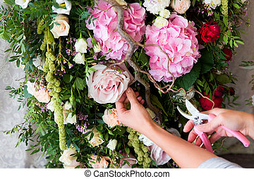 Florist at work. Woman making spring floral decorations the...
