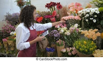 Florist checking prices with tablet in flower shop - Busy...