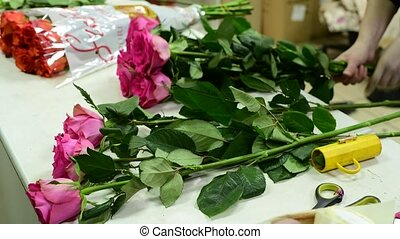 florist collects pink roses in bouquet - florist collects...