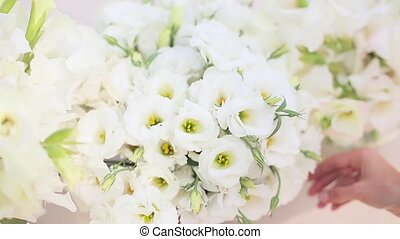 Florist corrects a white bouquet of flowers