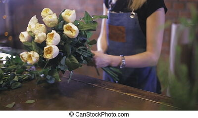 Florist creates bouquet of roses in floral shop