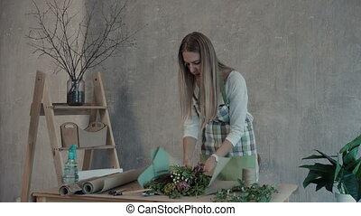 Florist creating beautiful flower arrangement -...