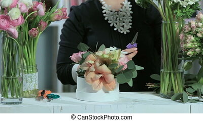 Florist cuts flowers, make flower bouquets in white table