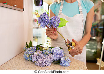 florist cuts  stems of flowers for a bouquet