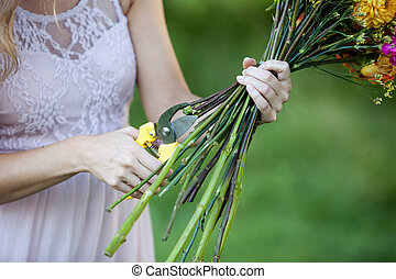 Florist cutting flower stems. ?loseup of female hand with shears