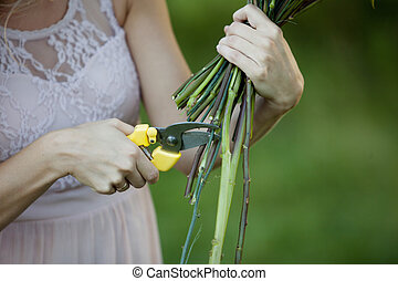 Florist cutting flowers stems, closeup of female hand with shears