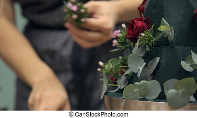 Florist decorates bouquet basis with beautiful small flowers.